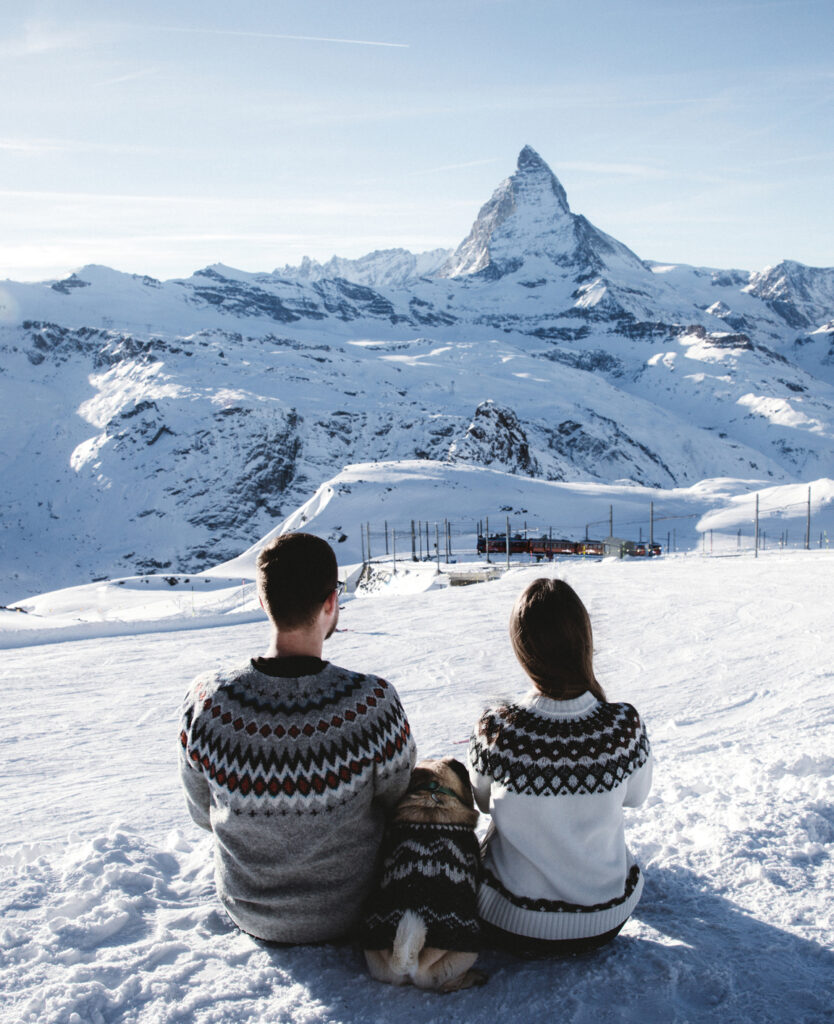 Happy woman,man and a small dog sitting in the mountains and looking at winter